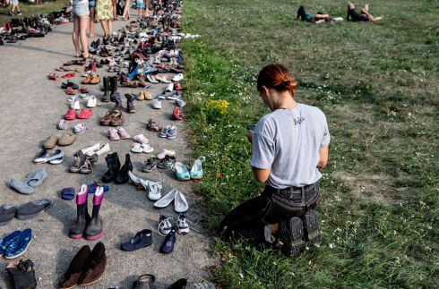 MASS RALLY: A girl sits next to an installation of shoes in rememberance of refugees who died crossing Mediterranean Sea during mass rally for an open society organized by action group Unteilbar (Indivisible) in Dresden, Germany on Saturday. Photograph: Filip Singer/EPA
