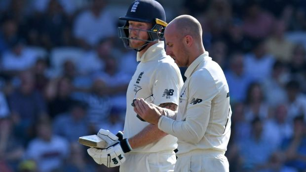 Jack Leach cleans his glasses as he and Ben Stokes speak during a break in play on the fourth day of the third Ashes Test at Headingley. Photograph: Paul Ellis/AFP/Getty Images
