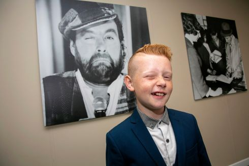 GRACING SHANNON AIRPORT: James Gillespie (11), grandson of late comic Brendan Grace (pictured behind him), at the Wall of Fame at Shannon Airport. Grace's wife Eileen, daughter Amanda and son-in-law Frank were also on hand to unveil the photo in the Shannon Airport gallery. Photograph: Arthur Ellis