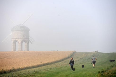JUST WALKING THE DOG: People walk their dogs through morning mist near Chesterton Windmill, in Warwickshire, England. Despite the mist, the current heatwave is set to continue for some parts of the UK after record-breaking weather at the weekend. Photograph: Jacob King/PA Wire