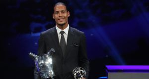 Liverpool's Dutch defender Virgil van Dijk poses with his trophies for Uefa's Men's Player of the Year and  Best Defender during the Champions League  group stages draw  in Monaco. Photograph:  Valery Hache/AFP/Getty Images