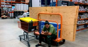 A woman watches her phone while stock up with hurricane supplies at Home Depot in Miami on Thursday. Photograph: Getty Images