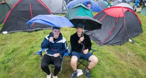 Calum McGrath and Aaron Miller, from Sligo, shelter from the rain at Electric Picnic 2019 in Stradbally. Photograph: Dave Meehan/The Irish Times