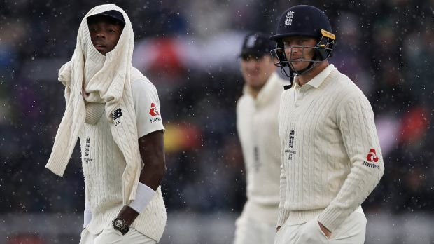 Jofra Archer and Jos Buttler of England leave the ground as rain stops play during day one of the fourth Test against Australia at Old Trafford. Photograph: Ryan Pierse/Getty Images