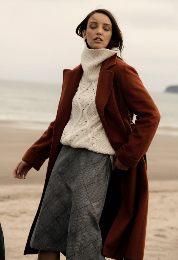Rust wrap collar coat €199, pearl cable sweater €79.99, black skirt €69.95