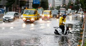A man rides a moped through a flooded street due to a typhoon in Tokyo on Monday. Photograph: Kyodo News via AP