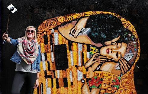 NO IRONY THEN: A bypasser uses her mobile to take a selfie including street art by Irish stencil artist ADW in Dublin city centre. The mural, based on the famed Kiss by Gustav Klimt, seeks to highlight the blight of mobile phone addiction. Photograph: Niall Carson/PA Wire