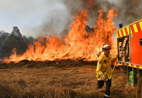 HOT WORK: New South Wales Rural Fire Service firefighters battle a blaze on Long Gully Road in the town of Drake, NSW, Australia. A number of homes have been destroyed by bushfires in the northern part of the state and in Queensland. Photograph: Darren England/EPA