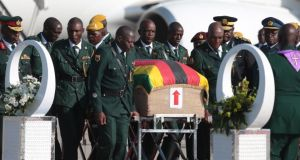 Members of Zimbabwe's presidential guard with the coffin containing the body of  Robert Mugabe, upon its arrival in Harare International airport. Photograph: Aaron Ufumeli/EPA