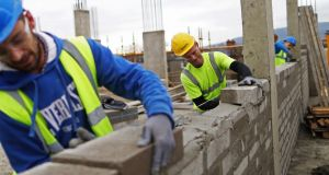 Construction workers lay bricks on the Cairn Homes Plc Marianella residential construction site in Dublin.