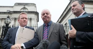 Victims' campaigner Raymond McCord (centre), with solicitors Ciaran O'Hare (left) and Paul Farrell outside the Royal Courts of Justice, Belfast. Photograph: Brian Lawless/PA W