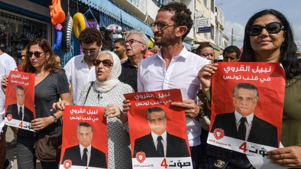 Najiba Karoui (second from left), mother of Tunisia's jailed presidential candidate Nabil Karoui, with his sister and others holding his election poster. Photograph: Fethi Belaid/AFP