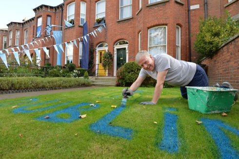 KEEPING THE FAITH: Liam Connolly puts the finishing touches to a neighbour's lawn on Dublin's Clonliffe Road in advance of the All-Ireland replay at Croke Park. Photograph: Alan Betson