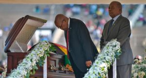 Former South African president Jacob Zuma (left) bows  as he stands by the casket of late former Zimbabwean president Robert Mugabe during a farewell ceremony held for family and heads of state at the National Sports Stadium in Harare on Saturday. Photograph: Tony Karumba/AFP/Getty