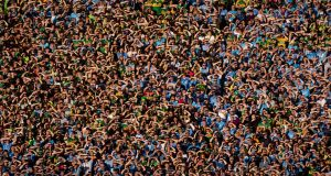 Supporters on Hill 16 shade their eyes against the sun during the All-Ireland final replay between Dublin and Kerry at Croke Park. Photograph:   Tom Honan