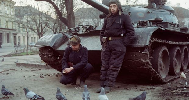 Romanian soldiers feed pigeons in front of their tank in Timisoara on December 25th, 1989. Photograph: Michel Gangne/AFP/Getty Images