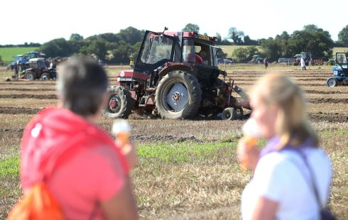 Punters lap up ice cream - and the continuing nice weather - during tractor ploughing at the Ploughing Championships. Photograph: Stephen Collins/Collins Photos