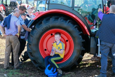 Luke Whyte (10), from Roscommon, escapes the heat in the shade of a tractor. Photograph: Nick Bradshaw