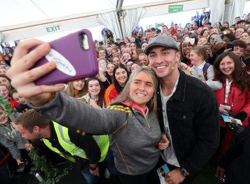 Lauren Delaney, from Loreto Secondary School in Kilkenny, takes a selfie with Greg O'Shea, winner of TV show Love Island, at the Grá Island contest at the National Dairy Council's tent. Photograph: Robbie Reynolds
