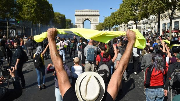 A man holds up a yellow vest in front of the Arc de Triomphe on the Champs Elysees in Paris during an anti-government demonstration on Saturday. Photograph: Lucas Barioulet/AFP/Getty