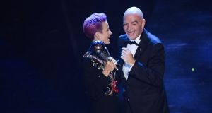 Megan Rapinoe is presented with her Fifa women's player of the year award from Fifa president Gianni Infantino at La Scala opera house in Milan. Photograph: Marco Bertorello/AFP/Getty Images