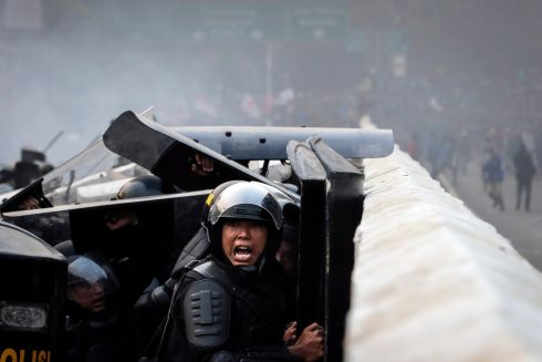 JAKARTA PROTESTS: An Indonesian police officer shouts during a clash with protesters outside the parliament building in Jakarta. Thousands of students staged protests across the country against a new law which changes its criminal code laws and weakens the country's anti-corruption commission. Photograph: Mast Irham/EPA