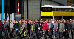 Workers walk through the gates of the Wrightbus plant in Ballymena on Wednesday. Photograph: Liam McBurney/PA Wire