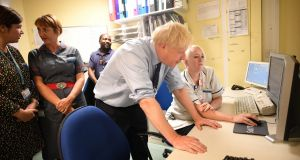 British prime minister Boris Johnson looks at a computer during a visit to a hospital in Harlow, north of London. Photograph: Getty Images