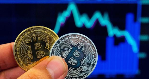A file photo shows a person holding a visual representation of the digital crypto-currency Bitcoin, at the Bitcoin Change shop in Tel Aviv, Israel. Photograph: JACK GUEZ / AFP)JACK GUEZ/AFP/Getty Images