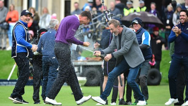 Victor Perez of France is sprayed with a bottle of champagne by Raphael Jacquelin following his victory at the Alfred Dunhill Links Championship at The Old Course. Photo: Mark Runnacles/Getty Images