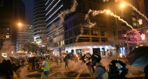 Tear gas canisters are lobbed at protesters during clashes with police following an earlier unsanctioned protest march through Hong Kong on Sunday. Photograph: Mohd Rasfan/AFP/Getty Images