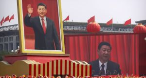 Participants cheer beneath a large portrait of Chinese president Xi Jinping during a parade to commemorate the 70th anniversary of the founding of Communist China in Beijing on Tuesday. Photograph: Mark Schiefelbein/AP