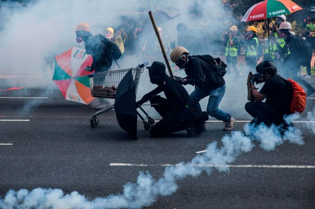 Protesters react among tear gas fired by police in the Sha Tin district of Hong Kong. Photograph: Isaac Lawrence / AFP)