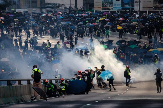 Demonstrators are shrouded in a cloud of tear gas outside the central government offices in the Admiralty district of Hong Kong. Photograph: Kyle Lam/Bloomberg