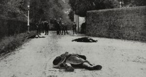 An RIC cadet and two members of Sinn Féin lying dead on the road, while in the background cadets are taking Sinn Féiners prisoners, Irish War of Independence, Tralee, Ireland. Photograph from The Illustrated London News, vol 157, no 4258, November 27, 1920.