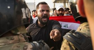 An Iraqi protestor gestures in front of security forces during a demonstration against state corruption, failing public services and unemployment, on Wednesday in the southern city of Basra. Photograph: Getty Images