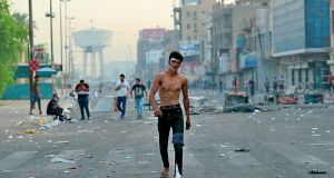 An Injured protester walks towards Tahrir Square to join anti-government protesters in central Baghdad, Iraq. Photograph: Hadi Mizban/AP