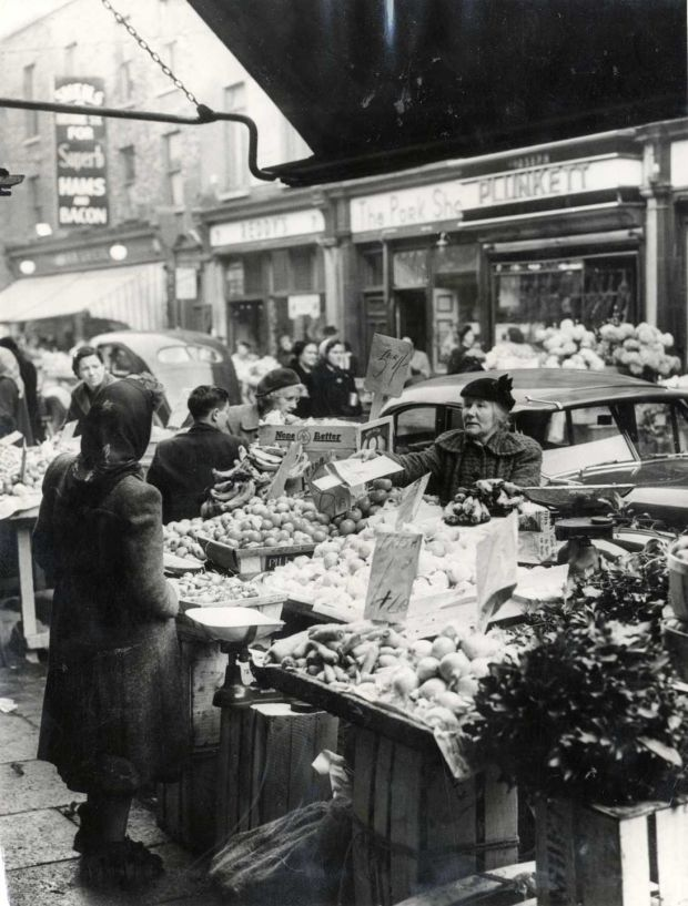 Vera Colgan (left, back) and Mary Colgan at their fruit and vegetable stand on Moore Street in 1955. Photograph: The Irish Times