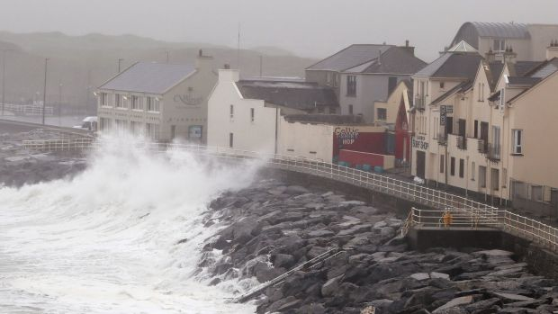 Waves crash agains the sea wall in Lahinch as thousands of homes and businesses have been left without power. Photograph: Brian Lawless/PA Wire.