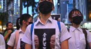 High school students chant slogans as they stick posters reading 'all people masked' on their uniforms as protesters gather in the heart of Hong Kong's commercial district on Friday. Photograph: Philip Fong/AFP via Getty