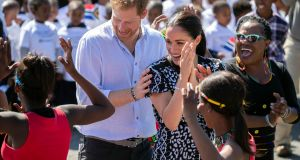 Britain's  Duchess of Sussex and Prince Harry (L), the Duke of Sussex, dance during a visit to Nyanga township in Cape Town, South Africa. Photograph: Facundo Arrizabalaga/EPA