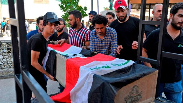 Mourners carry the Iraqi flag-draped coffin of a protester, who was killed amidst clashes in a demonstration, during his funeral in the central Iraqi city of Najaf on Friday. Photograph: Hadir Hamdani/AFP/Getty Images