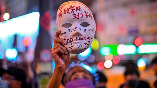 A woman holds a mask with slogans written on as protesters gather outside Mong Kok police station in Hong Kong on Saturday. Photograph: Philip Fong/AFP