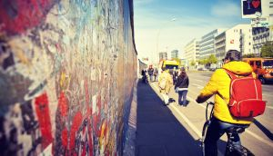A tourist on a bike rides along the East Side Gallery, an international memorial for freedom with paintings by artists from all over the world on one of the longest remaining sections of the Berlin Wall.