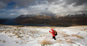 Hiker walking along Leenane Hill after snowfall with Killary Fjord and Mweelrea mountain in background.