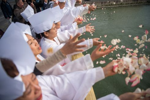TRAGEDY ON THE DANUBE: South Korean mourners throw petals into the River Danube from Margaret Bridge during a commemoration of victims of the Hableany boat disaster, in Budapest, Hungary. The Hableany sightseeing boat, carrying 33 South Korean tourists and two Hungarian staff, crashed into the Viking Sigyn cruise ship and sank in the river on May 29th last.  Only seven people survived. Photograph: Zoltan Balogh/EPA