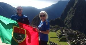 Lainey Broderick with her husband holding a Mayo flag in Macchu Piccu in Peru.