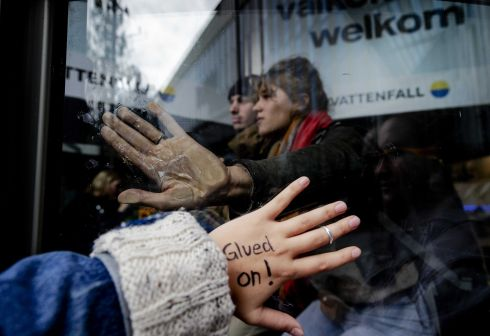 Climate activists from Extinction Rebellion glue themselves to the entrance door of the Vattenfall (formerly Nuon) head office near Amsterdam Bijlmer Arena in Amsterdam. Photograph: Robin Van Lonkhuijsen/EPA