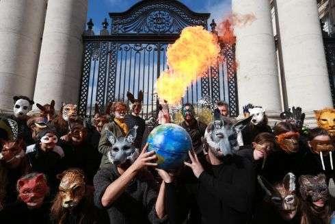 Climate change activists under the umbrella of Extinction Rebellion protest outside Government Buildings. Photograph: Laura Hutton/The Irish Times