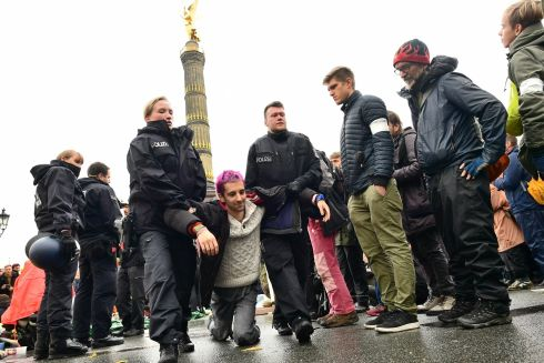 German police carry away an activist of the global environment movement Extinction Rebellion as they block a traffic junction around the victory column in Berlin. Photograph: Clemens Bilan/EPA